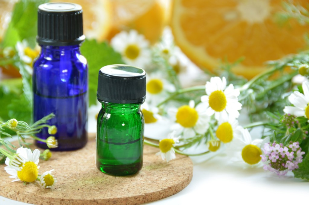 2 essential oil bottles and flowers