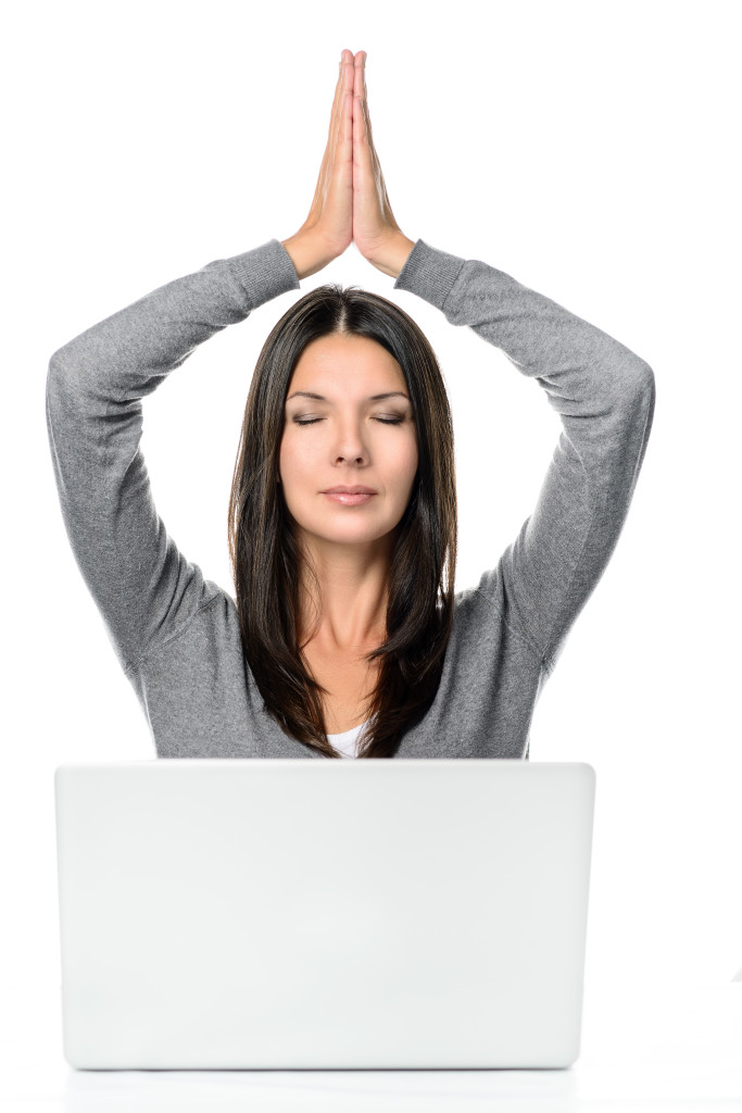 Pretty Long Hair Young Woman Meditating with Hands Over the Head and Closed Eyes In Front of a Laptop computer, isolated on white background