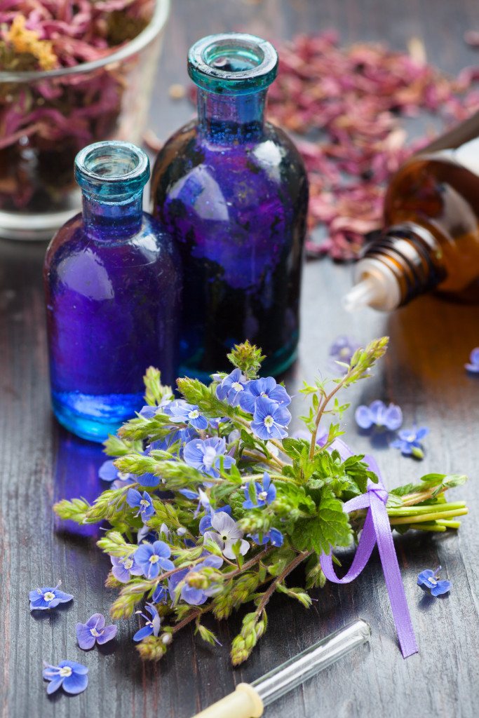 glass bottle of essential oil and blue healing flowers on wooden table