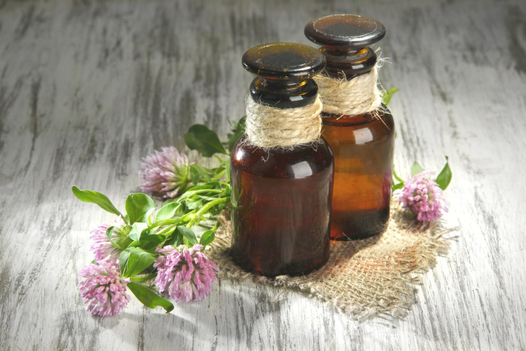Medicine bottles with clover flowers on wooden table