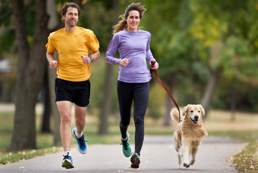 couple jogging outside with dog